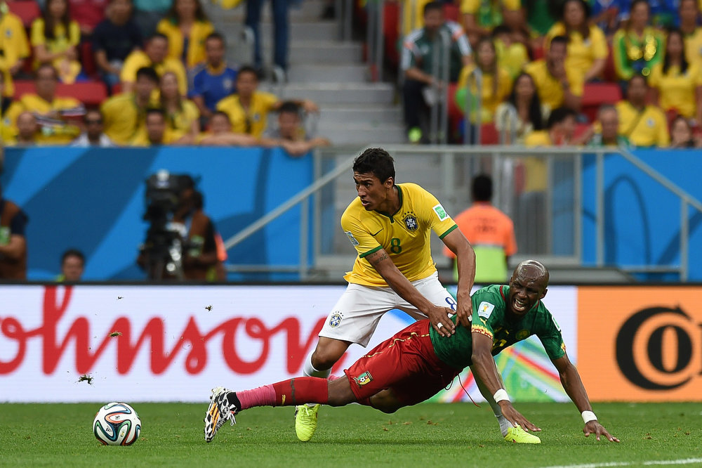 . Brazil\'s midfielder Paulinho (L) and Cameroon\'s midfielder Stephane Mbia vie for the ball during the Group A football match between Cameroon and Brazil at the Mane Garrincha National Stadium in Brasilia during the 2014 FIFA World Cup on June 23, 2014.   VANDERLEI ALMEIDA/AFP/Getty Images