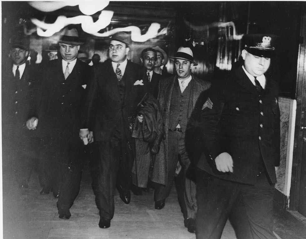 . Chicago crime boss Al Capone, center, in the custody of U.S. marshals, leaves the courtroom of Federal Judge James H. Wilkerson in Chicago on Oct. 24, 1931. He is facing tax evasion charges. (AP Photo)