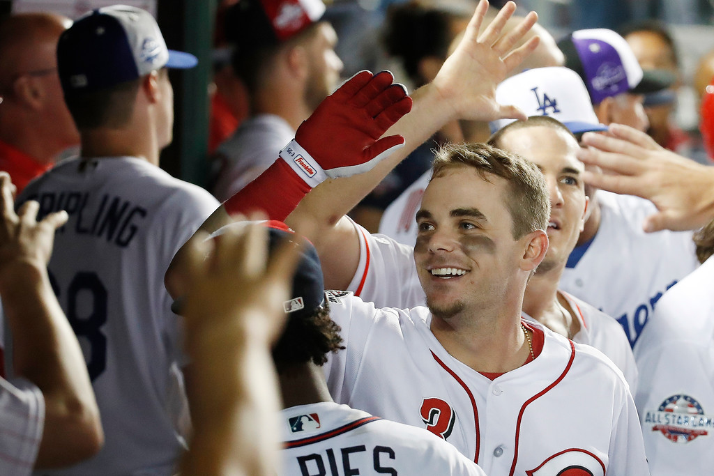 . Cincinnati Reds Scooter Gennett (3) celebrates in the dugout after his two-run homer in the ninth inning during the Major League Baseball All-star Game, Tuesday, July 17, 2018 in Washington. (AP Photo/Alex Brandon)