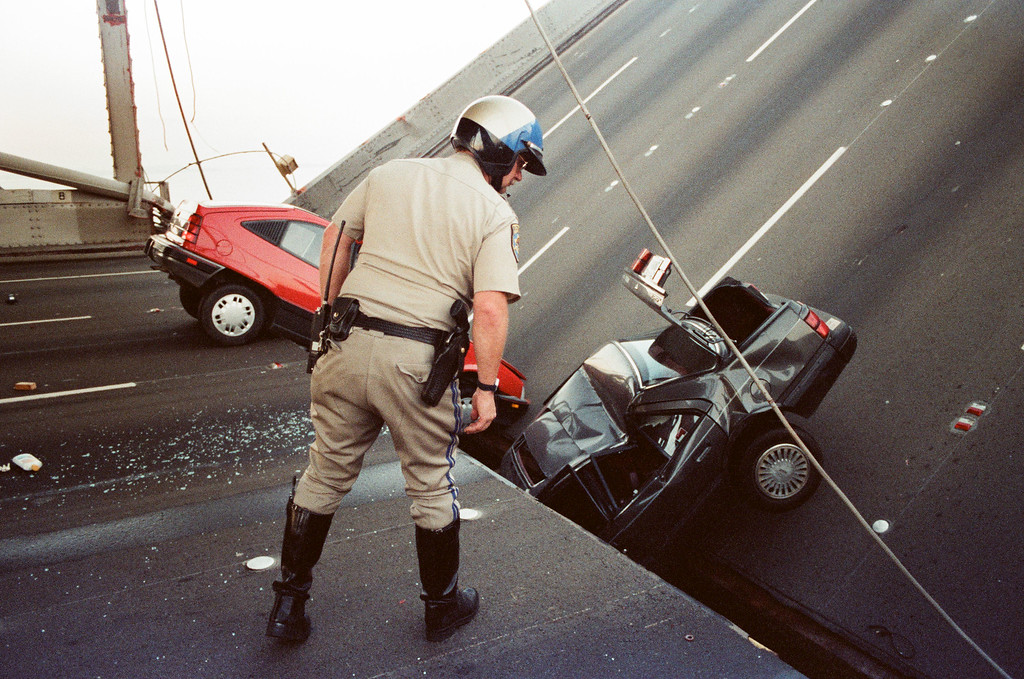 . FILE - In this Oct. 17, 1989 file photo, a California Highway Patrol officer checks the damage to cars that fell when the upper deck of the Bay Bridge collapsed onto the lower deck after the Loma Prieta earthquake in San Francisco.   (AP Photo/George Nikitin, File)