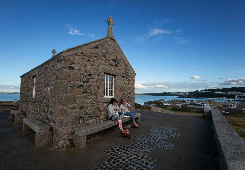 two young women eating fish and chips by an old chapel overlooking the small fishing village of St Ives.  St Ives, Cornwall, England, 2018