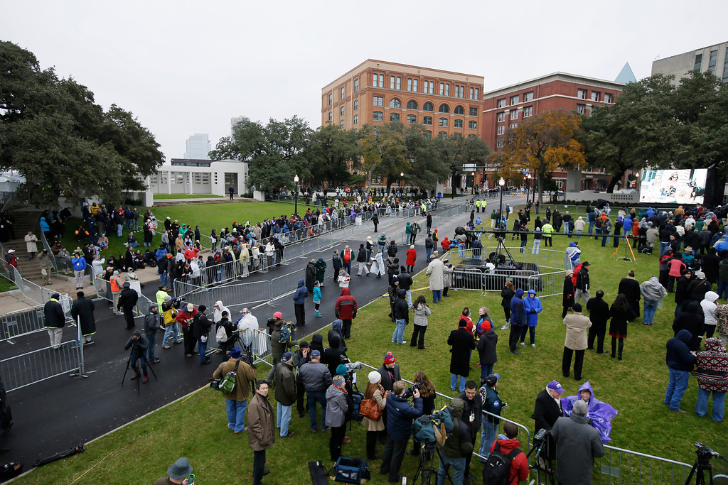 . A crowd moves into position before a ceremony to mark the 50th anniversary of the assassination of John F. Kennedy, Friday, Nov. 22, 2013, at Dealey Plaza in Dallas. President Kennedy\'s motorcade was passing through Dealey Plaza when shots rang out on Nov. 22, 1963. (AP Photo/Tony Gutierrez)