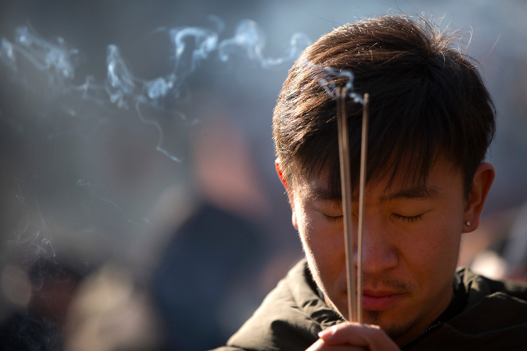 . A man burns incense as he prays on the first day of the Lunar New Year at the Lama Temple in Beijing, Friday, Feb. 16, 2018. Chinese around the world celebrated the arrival of the Year of the Dog on Friday with family reunions, firecrackers and traditional food. (AP Photo/Mark Schiefelbein)