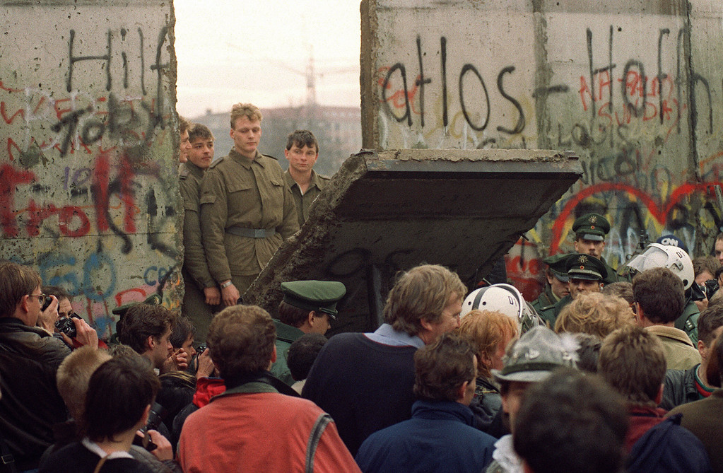 . West Berliners crowd in front of the Berlin Wall early 11 November 1989 as they watch East German border guards demolishing a section of the wall in order to open a new crossing point between East and West Berlin, near the Potsdamer Square.   (Photo credit GERARD MALIE/AFP/Getty Images)