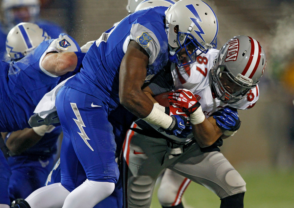 . Air Force defensive back Christian Spears, left, stops UNLV wide receiver Maika Mataele just short of the end zone after his pass reception in the first quarter of an NCAA football game at Air Force Academy, Colo., on Thursday, Nov. 21, 2013. (AP Photo/David Zalubowski)