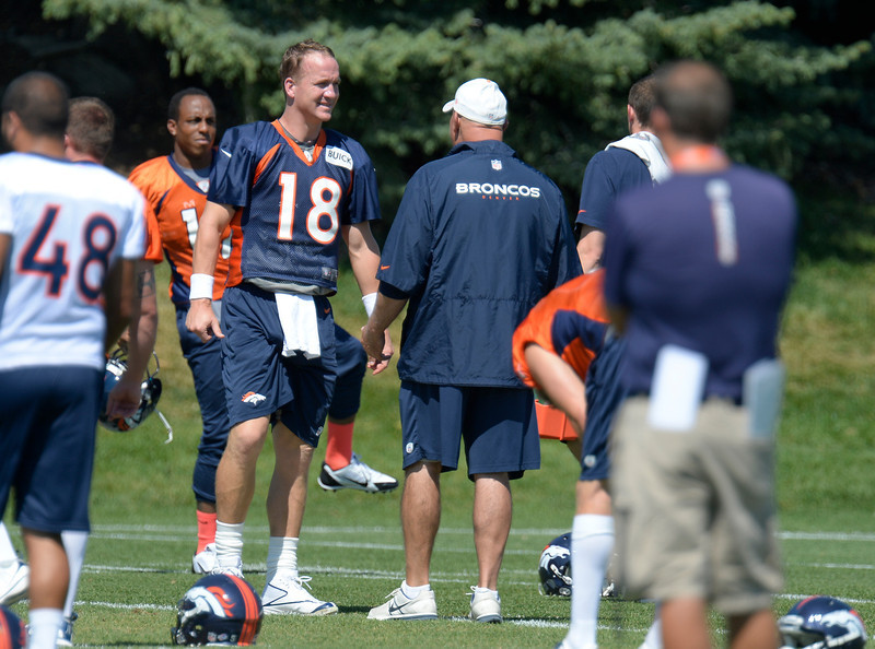 . Denver Broncos quarterback Peyton Manning (18) talks with offensive line coach Dave Magazu during practice August 19, 2013 at Dove Valley (Photo by John Leyba/The Denver Post)