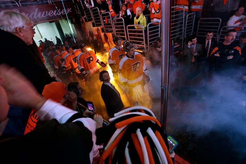 . Fans watch as the Philadelphia Flyers wait in bright lights to enter the ice for an NHL hockey game against the Pittsburgh Penguins Saturday, Jan.19, 2013, in Philadelphia. (AP Photo/Mel Evans)