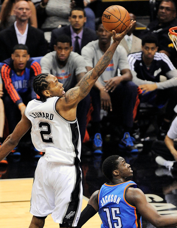 . San Antonio Spurs forward Kawhi Leonard (2) shoots over Oklahoma City Thunder guard Reggie Jackson during the second half of Game 1 of a Western Conference finals NBA basketball playoff series, Monday, May 19, 2014, in San Antonio. San Antonio won 122-105. (AP Photo/Darren Abate)