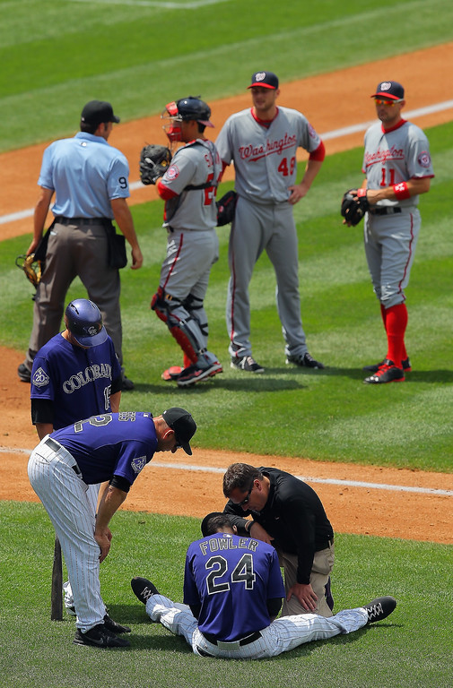 . Assistant athletic trainer Scott Gehret attends to Dexter Fowler #24 of the Colorado Rockies after being hit by a pitch by starting pitcher Ross Detwiler #48 of the Washington Nationals in the third inning at Coors Field on June 13, 2013 in Denver, Colorado. Fowler took the base but left the game in the fourth inning.  (Photo by Doug Pensinger/Getty Images)