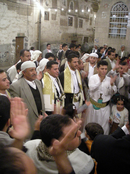 two grooms, in gold embroidered scarfs, at a street multiple wedding celebration, old Sana'a