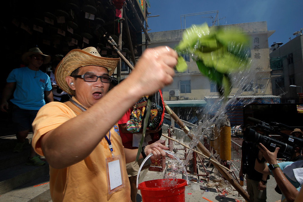 . A villager performs a ritual during a parade on the outlying Cheung Chau island in Hong Kong to celebrate the Bun Festival Tuesday, May 22, 2018. Thousands of local residents and tourists flocked to an outlying island in Hong Kong to celebrate a local bun festival on Tuesday despite the recording-breaking heat.  The festival features a parade with children dressed as deities floated on poles. Later on Tuesday, contestants will take part in bun-scrambling competition. They will race up a 14-meter bamboo tower to snatch as many plastics buns as possible. Buns that are higher up are worth more points.  (AP Photo/Kin Cheung)