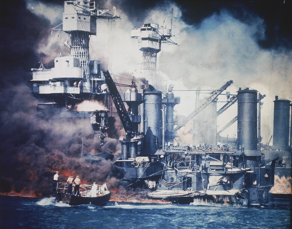 . A small boat rescues a USS West Virginia crew member from the water after the Japanese bombing of Pearl Harbor, Hawaii on Dec. 7, 1941 during World War II.  Two men can be seen on the superstructure, upper center.  The mast of the USS Tennessee is beyond the burning West Virginia.  (AP Photo)
