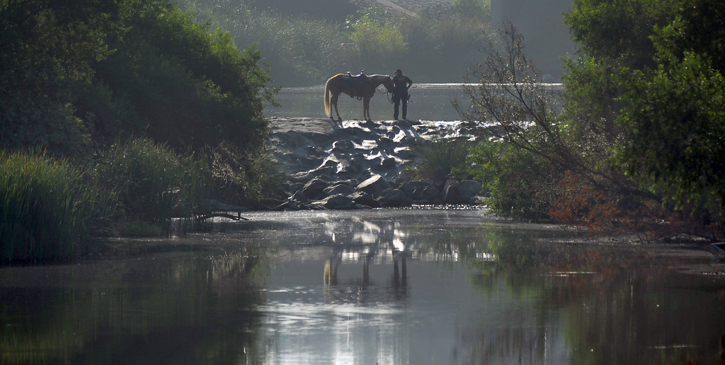 . A Los Angeles County Sheriff\'s Mounted Deputy stops on the trail as they search for homeless individuals camping in the river bed area of the San Gabriel River near South El Monte on Thursday September 12, 2013. (Whittier Daily News/Staff Photo by Keith Durflinger)