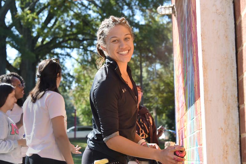 Alpha Kappa Alpha service chair Makaylla Binter, a studio art and biology double major, found time last Saturday morning to help paint a mural at the Ada Jenkins Center. (Bill Giduz photo)