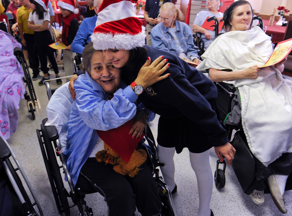. Linda Gonzales, is greeted with a hug by Maria Carrillo, 9, after students and parents from the Denver Center for International Studies at Ford Elementary School spend a Saturday singing holiday songs in three different languages to the residents of the Kindred Care nursing home.  (Photo by Kathryn Scott Osler/The Denver Post)
