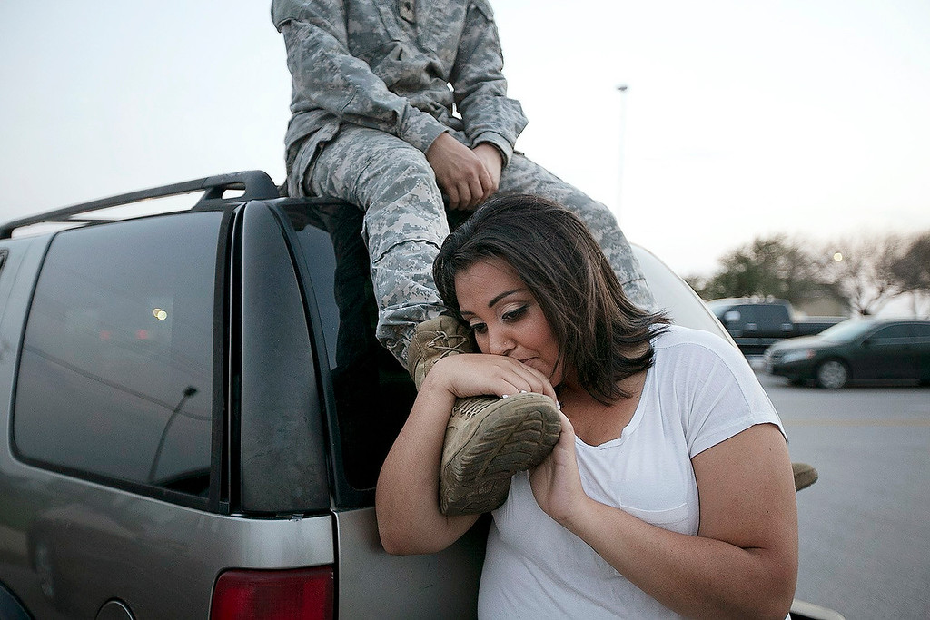 . Lucy Hamlin leans on her husband\'s foot, Specialist Timothy Hamlin, as they wait to be allowed back onto Fort Hood, Texas, where they reside on Wednesday, April 2, 2014. A shooting occurred on the base with at least four dead and 14 injured according to the officials. (AP Photo/Austin American-Statesman, Deborah Cannon)