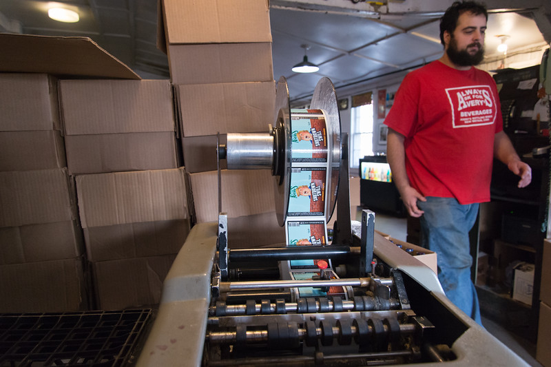 01/15/19  Wesley Bunnell | Staff  Avery's Soda employee Forrest Zirpolo walks past the company's label machine featuring labels for their limited edition flavor Shutdown Swill. The labels feature a caricature of President Trump and come with either red or blue caps to represent the Democratic and Republican parties.