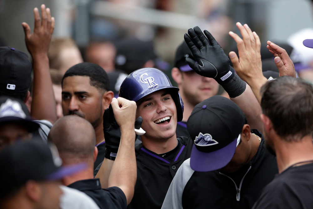 . Colorado Rockies\' Ryan Casteel, center, is greeted by teammates after hitting a home run against the Arizona Diamondbacks during the third inning in a spring training baseball game Friday, Feb. 28, 2014, in Scottsdale, Ariz. (AP Photo/Gregory Bull)