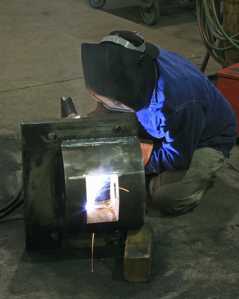 A worker welds on the articulation joint.  The original was trashed in a smashup that ruined the tank frame.  Its replacement was not a match for the half of the joint that evidently was not broken.  This new fabrication matches the original. March 2007