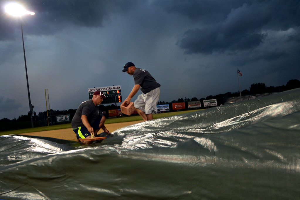 . Members of the grounds crew secure tarps over the mound on the ballfield with heavy thunder storms canceling the Pennsylvania Little League State Tournament evening game at Palmer Park on Wednesday July 23,2014.Photo by Mark C Psoras/The Reporter