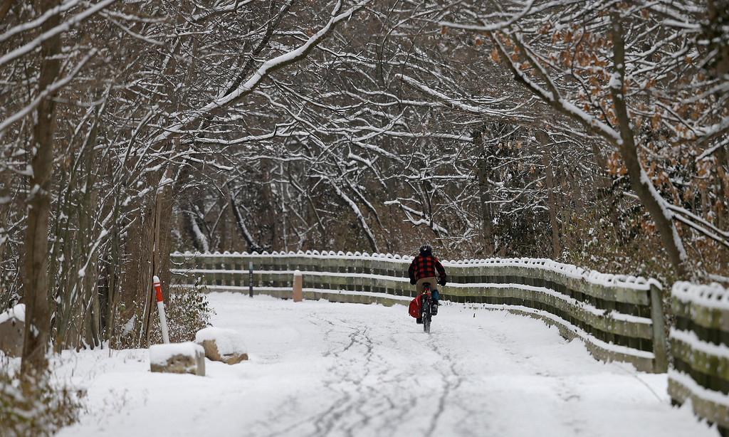 . A bicyclist rides his bike on the Monon Trail following a winter storm Friday, Dec. 6, 2013, in Indianapolis. Several inches of snow fell on central and southern Indiana, making driving treacherous and leading to at least two fatal crashes. (AP Photo/Darron Cummings)