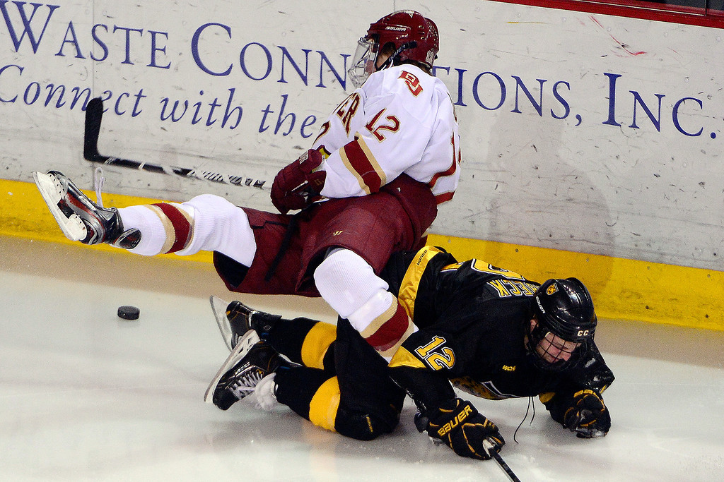. DENVER, CO - MARCH 17: Archie Skalbeck (12) of the Colorado College Tigers trips up Ty Loney (12) of the University of Denver Pioneers during the third period of action. The University of Denver loses 4-3 to Colorado College during the WCHA playoffs at Magness Arena. (Photo by AAron Ontiveroz/The Denver Post)