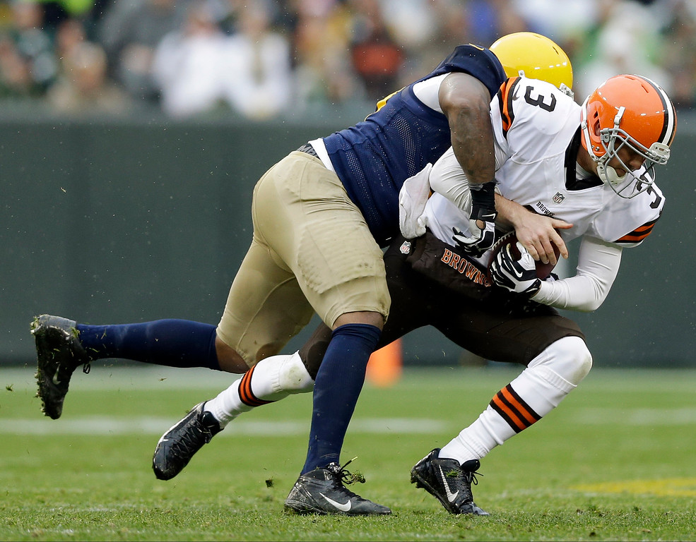 . Green Bay Packers\' Mike Daniels sacks Cleveland Browns quarterback Brandon Weeden during the first half of an NFL football game Sunday, Oct. 20, 2013, in Green Bay, Wis. (AP Photo/Tom Lynn)