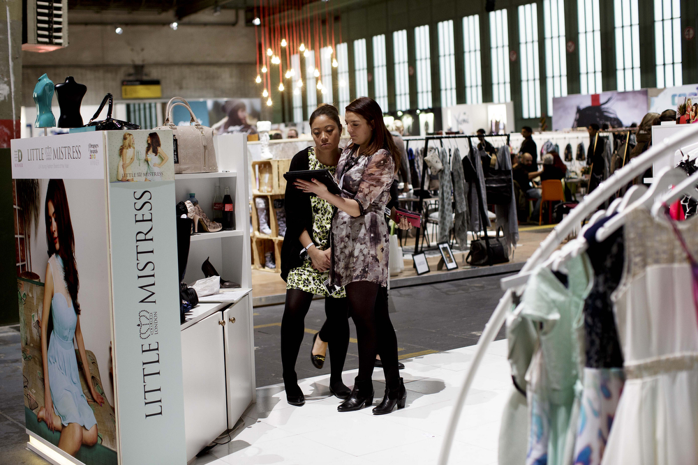 . Representatives of the label Little Mistress talk  at the Little Mistress brand stand at the Bread and Butter trade show at the former Tempelhof airport during Mercedes-Benz Fashion Week Autumn/Winter 2014/15 on January 15, 2014 in Berlin, Germany.  (Photo by Carsten Koall/Getty Images)