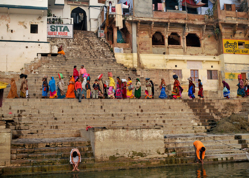 Pilgrims walk along a ghat on the Ganges. Early morning in Varanasi.