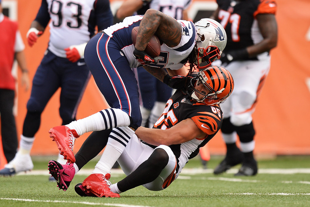 . Tyler Eifert #85 of the Cincinnati Bengals tackles Brandon Spikes #55 of the New England Patriots after Spikes intercepted the ball in the first quarter at Paul Brown Stadium on October 6, 2013 in Cincinnati, Ohio.  (Photo by Jamie Sabau/Getty Images)