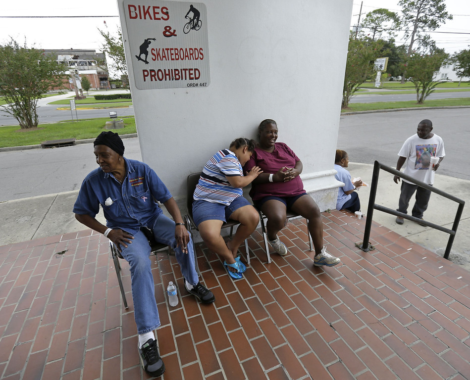 . Lillian Edwards, left, Zanaya Reddick, and Christine Encalade, right,  all of Pointe a la Hache, La., sit at an evacuation shelter, in anticipation of Tropical Storm Karen, Saturday, Oct. 5, 2013. The East Bank of Plaquemines Parish has been under a mandatory evacuation, which has been downgraded to a voluntary evacuation. (AP Photo/Gerald Herbert)