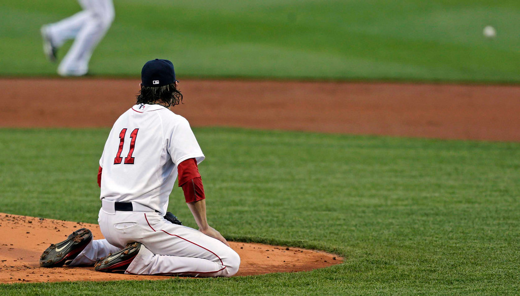 . Boston Red Sox starting pitcher Clay Buchholz watches as a ball hit for an RBI single by Minnesota Twins\' Justin Morneau, which Buchholz deflected, rolls toward the outfield during the first inning. (AP Photo/Charles Krupa)
