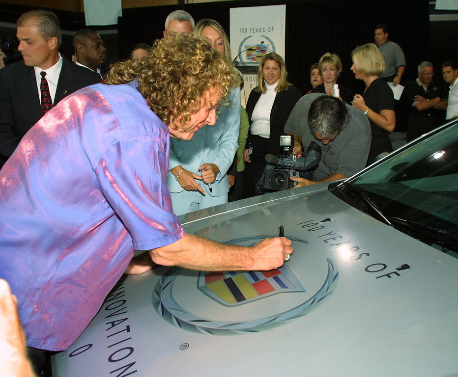 . Led Zeppelin lead singer Robert Plant  signs the hood of a 2003 Cadillac CTS at the General Motors world headquarters August 22, 2002 in Detroit, Michigan . Plant, who was in Detroit for a concert, attended a GM celebration of company\'s 100th anniversary of the Cadillac line.  (Photo by Bill Pugliano/Getty Images)