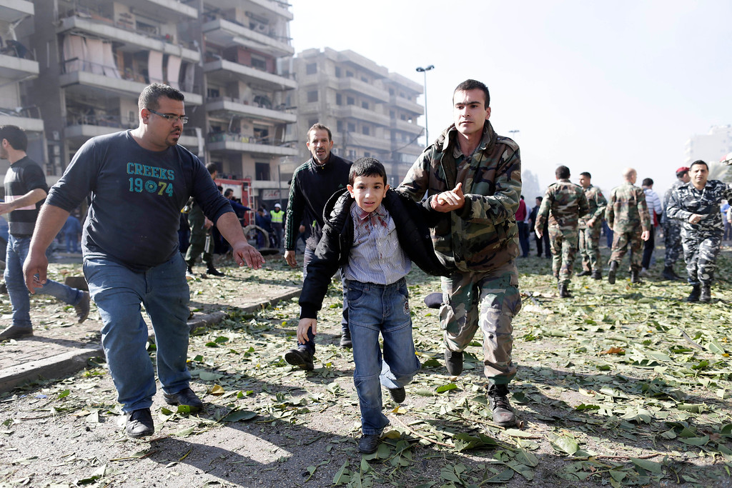 . A Lebanese soldier helps an injured boy away from the site of a car bombing in the suburb of Beir Hassan, Beirut, Lebanon, Wednesday, Feb. 19, 2014. (AP Photo/Hassan Ammar)