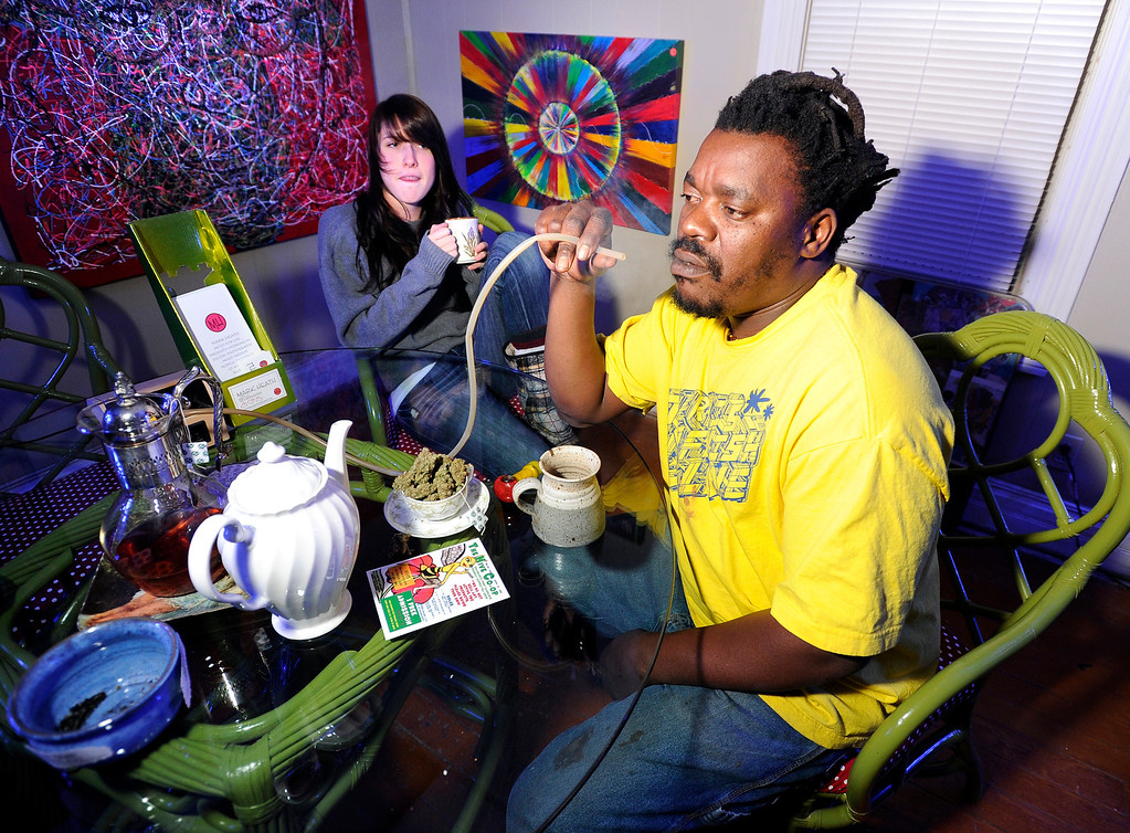 . Bongo Love, of Lafayette, takes a hit of marijuana from a vaporizer while sitting next to Kyrie Wozab, of Louisville, on Wednesday, Jan. 2, at The Hive Co-Op Cannabis Club in Lafayette. Jeremy Papasso/Boulder Daily Camera