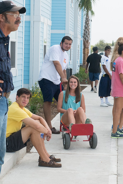 Mollee Hendrix(center) takes a break on the dolly during Move In Day at Momentum Village.