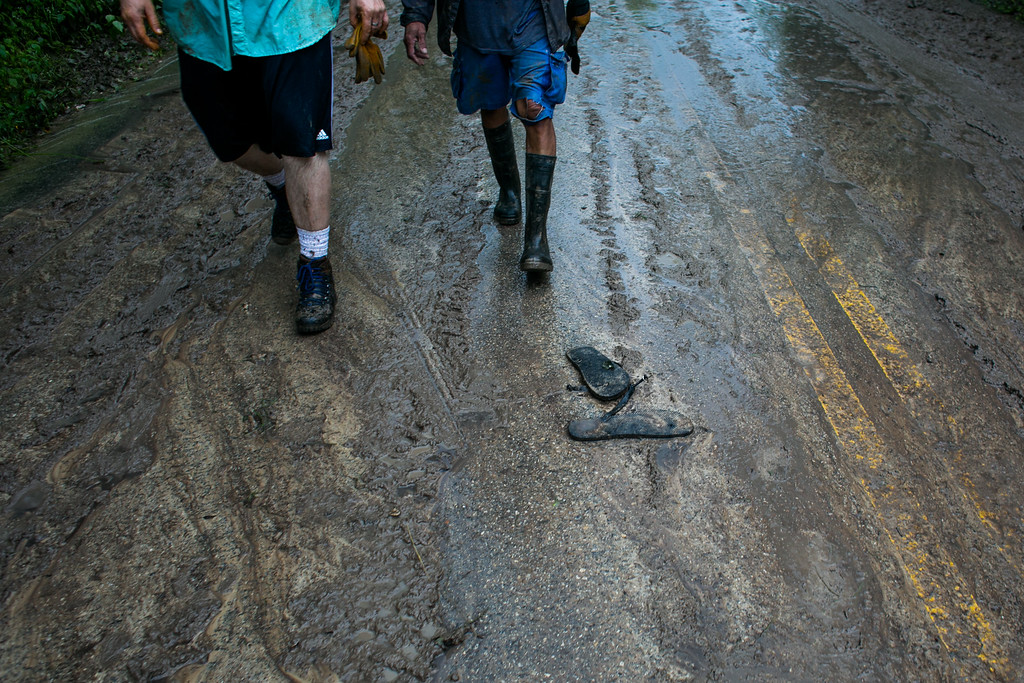 . WIMBERLEY, TX - MAY 25:   Residents walk along Texas Ranch Road 12 covered in residual mud on May 25, 2015 in Wimberly, Texas.  Texas Gov. Greg Abbott toured the damage zone where one person is confirmed dead and at least 12 others missing in flooding along the Rio Blanco, which reports say rose as much as 40 feet in places, caused by more than 10 inches of rain over a four-day period. The governor earlier declared a state of emergency in 24 Texas counties.  (Photo by Drew Anthony Smith/Getty Images)