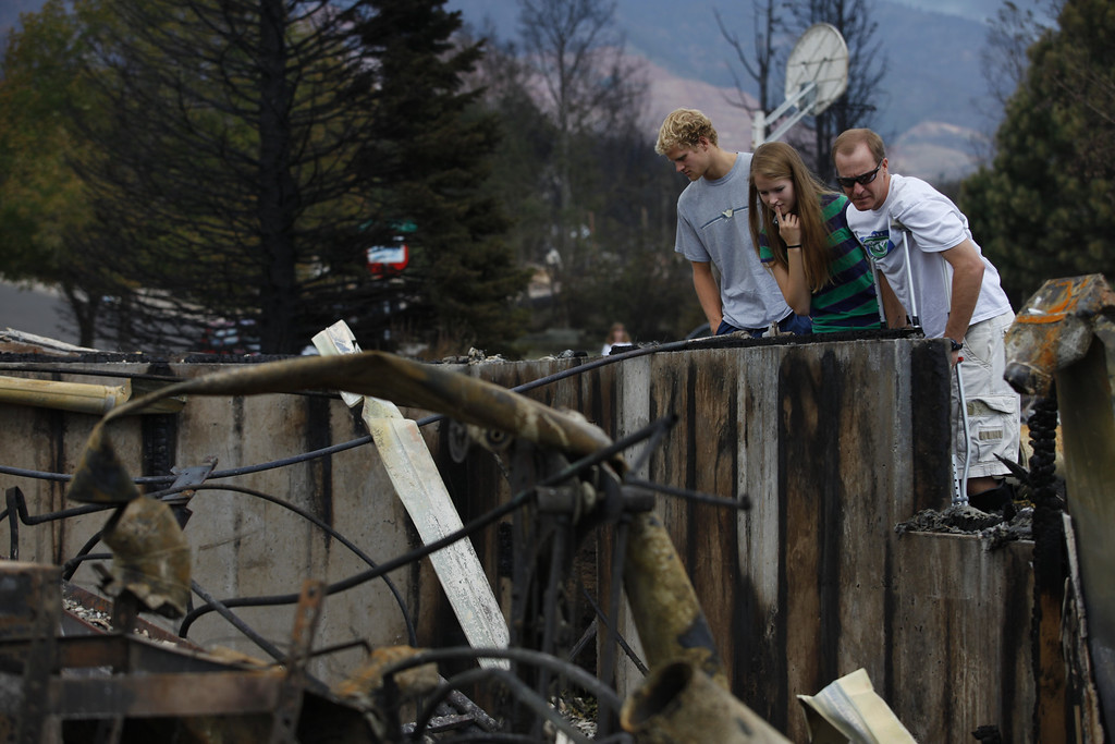 . From left, Eric, Krista and Mark Albers examine the remnants of their home in the Mountain Shadows subdivision on Sunday, July 1, 2012. Their home was destroyed in the Waldo Canyon fire. Stephen Mitchell, The Denver Post
