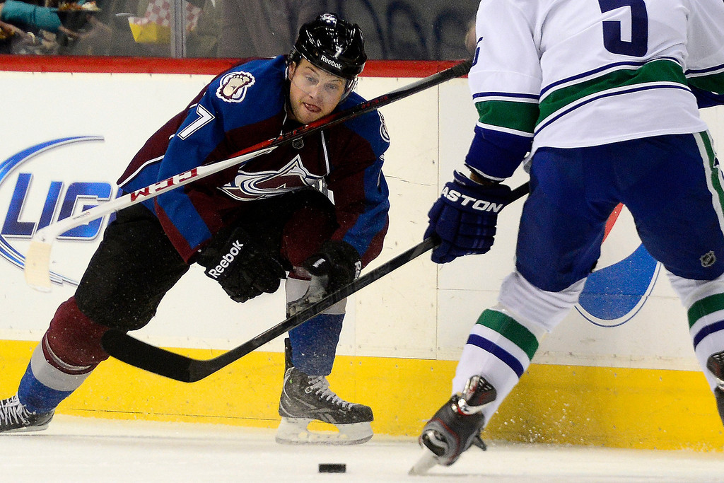 . DENVER, CO - MARCH 24: John Mitchell (7) of the Colorado Avalanche loses his stick while defending Jason Garrison (5) of the Vancouver Canucks during the first period of action. Colorado Avalanche versus the Vancouver Canucks at the Pepsi Center. (Photo by AAron Ontiveroz/The Denver Post)