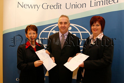 Marian Hollywood (senior credit controller newry credit union) left and Rita Copas (money management manager newry credit union) receive Training Certificates for Money Management from Martin Mc Donald (treasurer newry credit union), 07W5N68