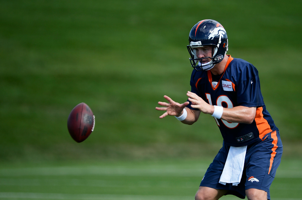 . Denver Broncos quarterback Peyton Manning (18) takes the snap during drills on the first day of the Denver Broncos 2014 training camp July 24, 2014 at Dove Valley. (Photo by John Leyba/The Denver Post)