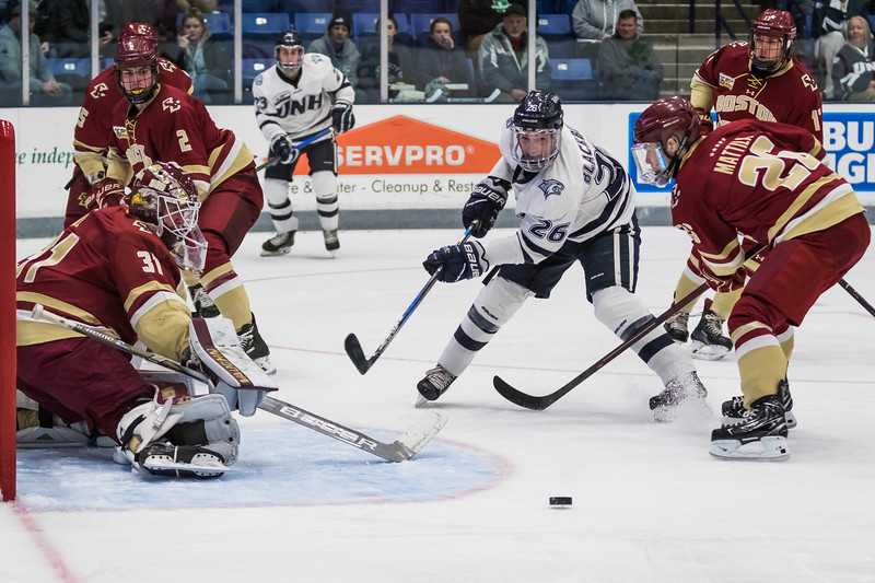 UNH's Liam Blackburn (26) has his shot blocked by BC goalie Joseph Woll (31) during Hockey East action Saturday night in Durham. [Scott Patterson/Fosters.com]