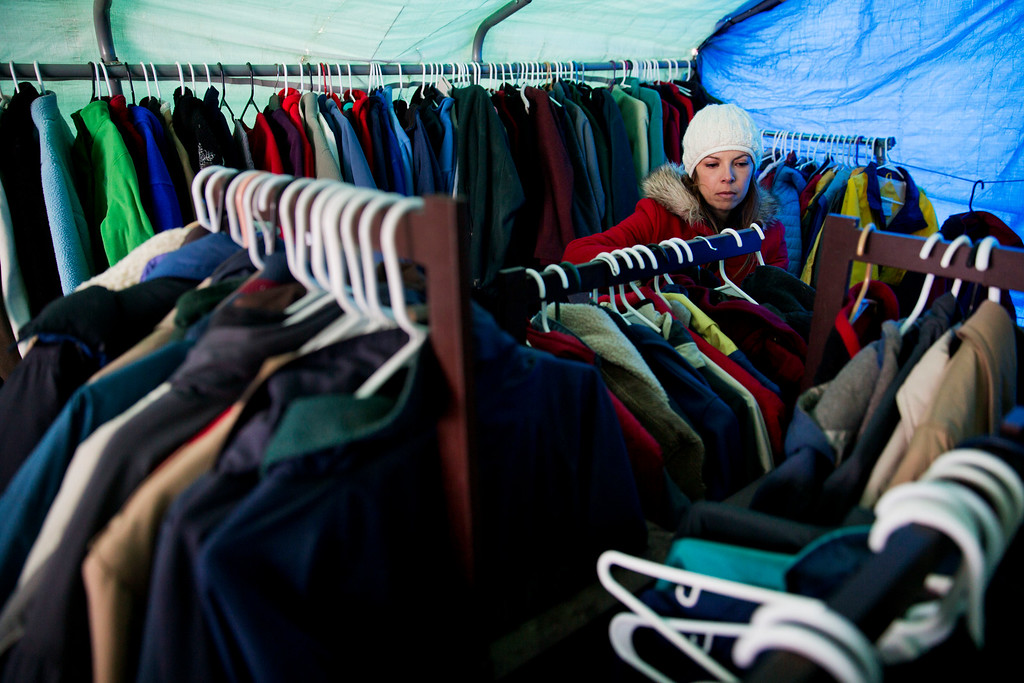 . Lindsey Denison, of Los Angeles, volunteers to hang up donated clothing at the Oceti Sakowin camp where people have gathered to protest the Dakota Access oil pipeline in Cannon Ball, N.D., Friday, Dec. 2, 2016. (AP Photo/David Goldman)