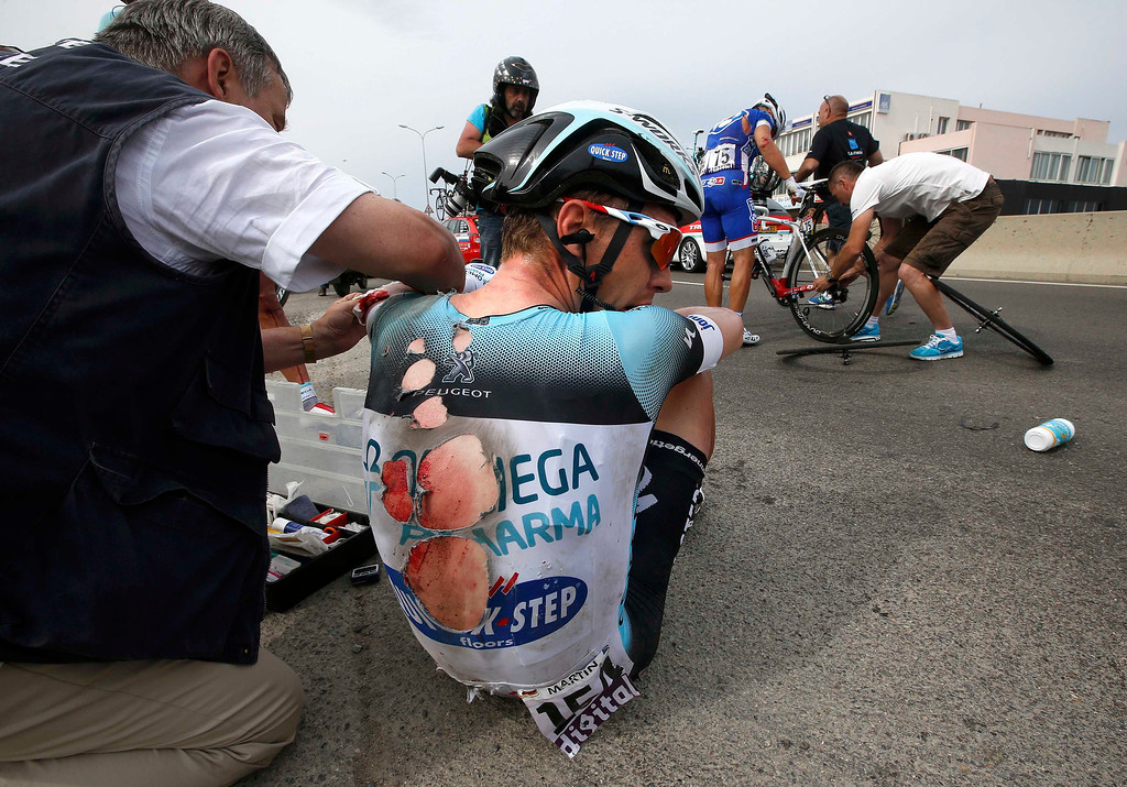 . Omega Pharma-Quick Step team rider Tony Martin of Germany sits on the road after he fell at 5 kilometers before the finish of the 213 km first stage of the centenary Tour de France cycling race from Porto-Vecchio to Bastia, on the French Mediterranean island of Corsica June 29, 2013.    REUTERS/Eric Gaillard
