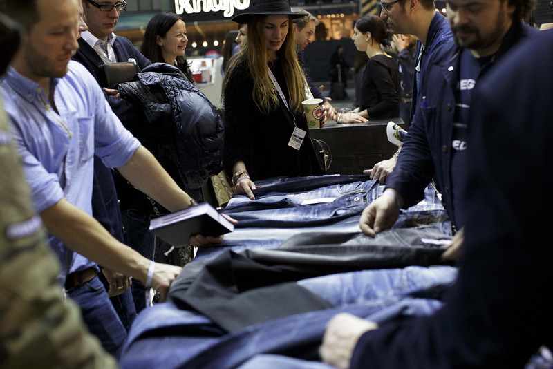 . A representative of the label Mustang tells to participants about several Jeans materials at the Mustang brand stand at the Bread and Butter trade show at the former Tempelhof airport during Mercedes-Benz Fashion Week Autumn/Winter 2014/15 on January 15, 2014 in Berlin, Germany.  (Photo by Carsten Koall/Getty Images)