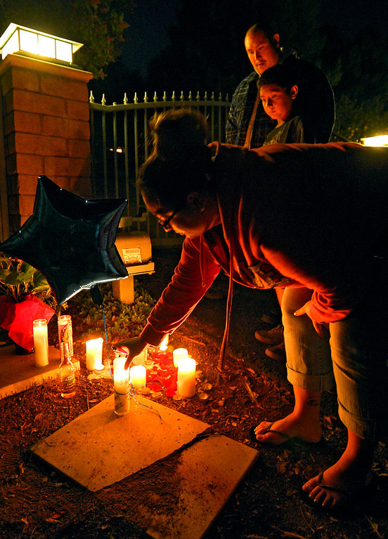 . Cecy Robles places candle and a balloon in front of what is believed to be the home of singer Jenni Rivera as Ruben Robles, top, and Anthony Robles watch on Sunday, Dec. 9, 2012, in the Encino section of Los Angeles. The wreckage of a small plane believed to be carrying Rivera, the U.S-born singer whose soulful voice and unfettered discussion of a series of personal travails made her a Mexican-American superstar, was found in northern Mexico on Sunday. Authorities said there were no survivors. (AP Photo/Mark J. Terrill)