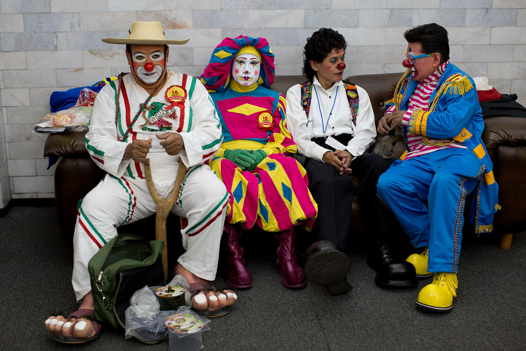 . In this Monday, Oct. 21, 2013 photo, clowns sit on a couch during a break on the first day of the 17th International Clown Convention at a theater in Mexico City. Clowns from Latin America gathered in Mexico City to enter competitions, exchange experiences and take workshops in order to brush up on their clown techniques and learn new tricks.  (AP Photo/Dario Lopez-Mills)
