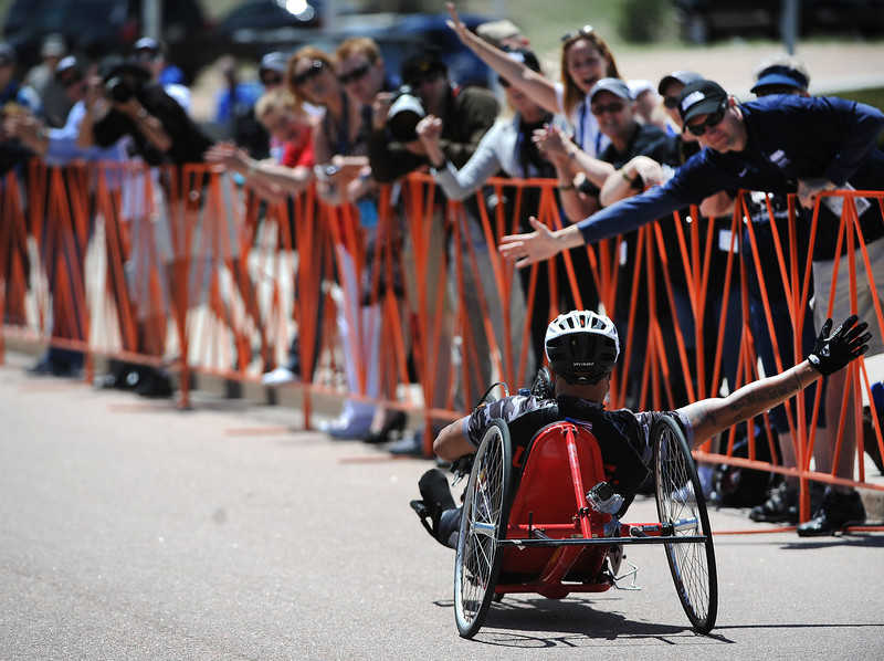 . Ronnie Jimenez gets high fives from the crowd after winning the men\'s hand cycle race.  The fourth annual Warrior Games cycling event took started and finished at Falcon Stadium on the grounds of the Air Force Academy in Colorado Springs, CO on May 12, 2013.  HRH Prince Harry was on hand to start the race as well as to hand out medals at the finish line.   A total of 260 wounded, ill and injured service members and veterans came to compete in the week long games.  Members of the Army, Marine Corps, Navy/Coast Guard/Air Force. Special Operations and the British Armed Forces all took part in the competition.  Other events included in the Warrior Games are shooting, sitting volleyball, track & field and wheelchair basketball.  (Photo by Helen H. Richardson/The Denver Post)