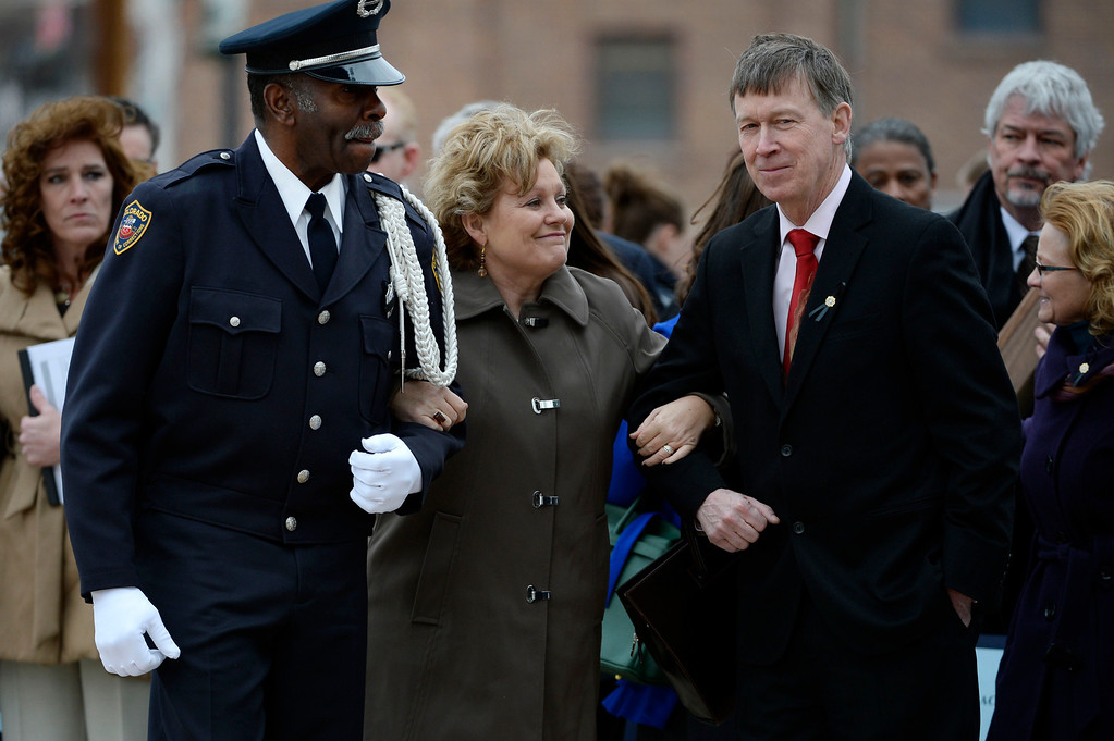 . Lisa Clements, wife of fallen Department of Correction executive director, Tom Clements, center, cracks a half smile as Colorado Department of Corrections Honor Guard member, Harry Campbell, left, and Colorado Governor, John Hickenlooper, right, escort Lisa Clements, away from the Colorado Department of Corrections Fallen Officer Memorial honoring her  at the Territorial Correctional Facility park Saturday morning, March 15, 2014.   (Photo By Andy Cross / The Denver Post)