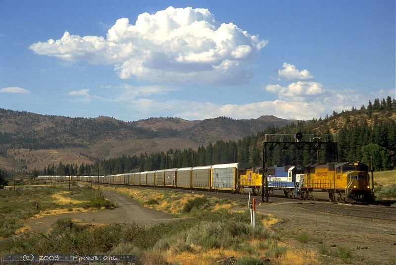 Seldom do the mountains permit a view of the full train. This westbound autorack consist has an Oakway leaser as it passes Essex, NV.